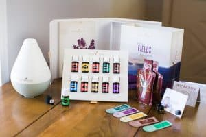 image of wooden table with Young Living Premium Starter kit displayed with oils, diffuser and samples