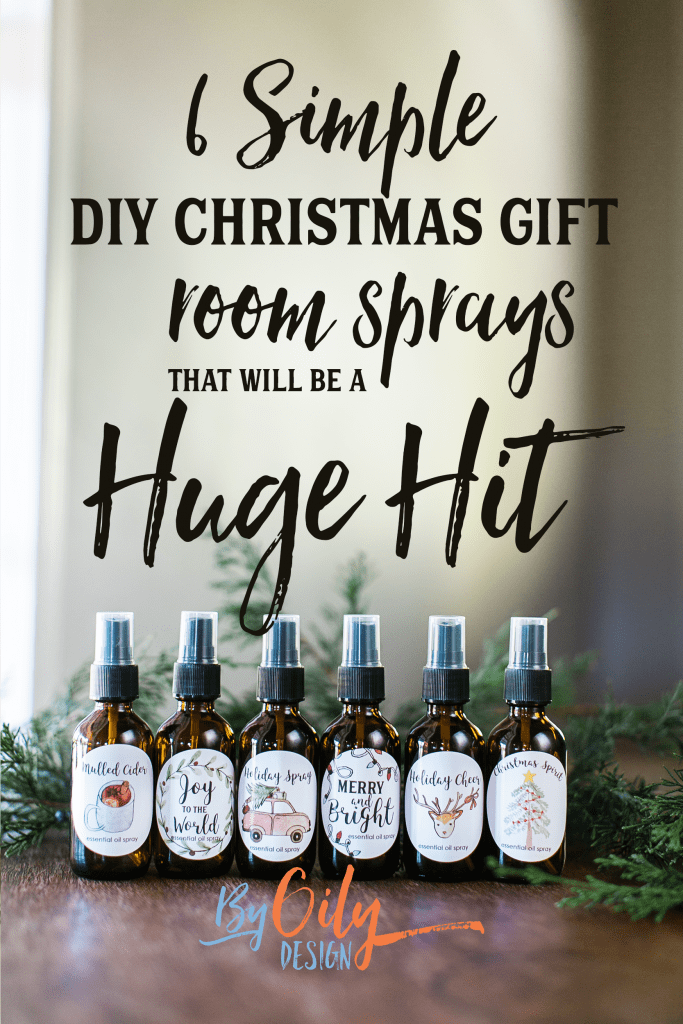 6 Essential Oil room spray bottles on a wood table with varying Christmas labels and evergreen branches.