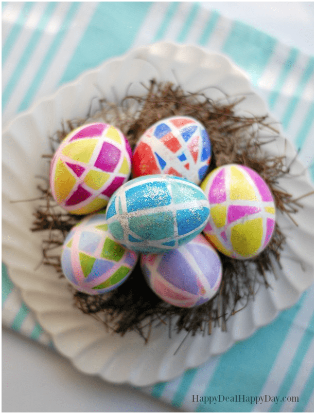 colorful Easter eggs on a wooden nest and white plate