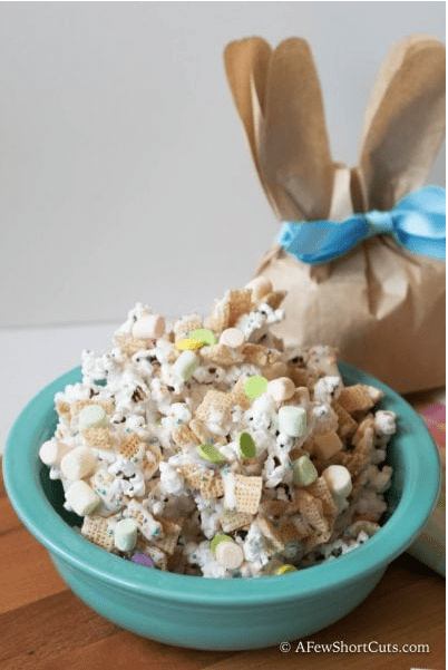 blue bowl with popcorn mix and brown paper bag in the shape of a bunny