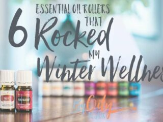 Essential oils good for winter wellness sitting by an essential oil roller bottle