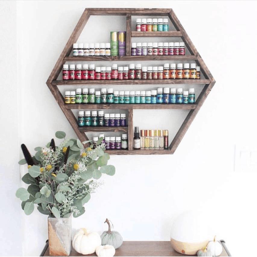 Large wooden hexagon shelf holding bottles of essential oils