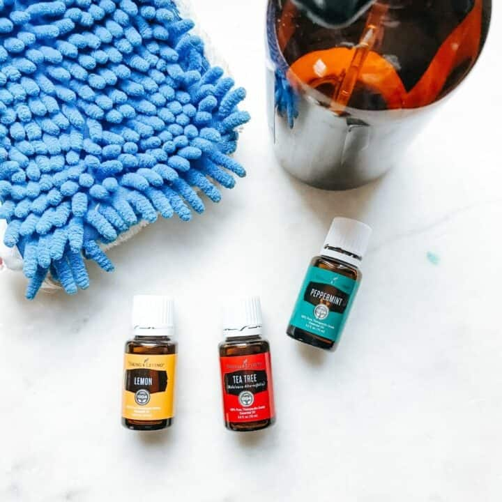 lemon, Tea Tree and peppermint oils laying on a white surface next to a mop head and glass bottle showing tools needed for making natural floor cleaner