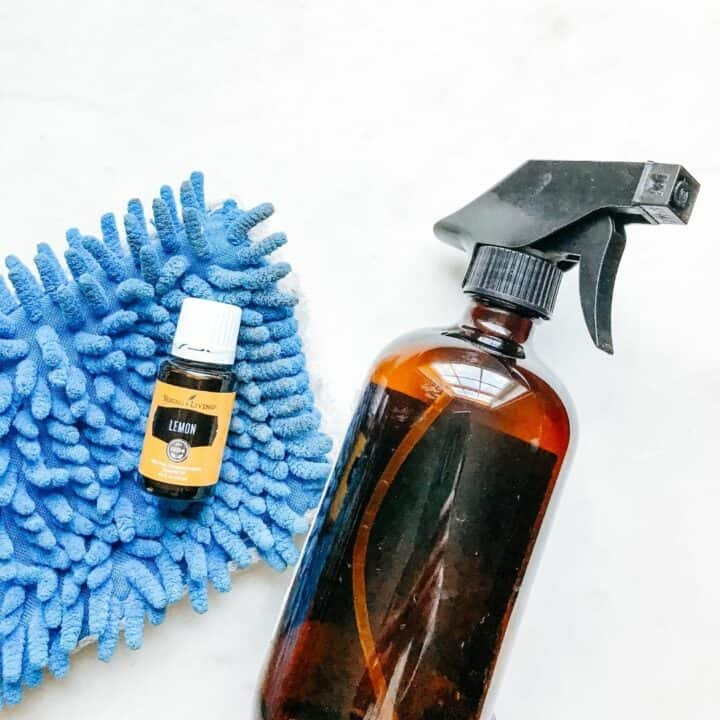 Lemon essential oil, mop and spray bottle showing tools to make homemade laminate floor cleaner.