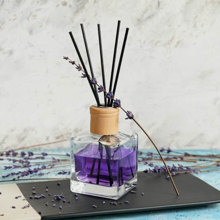 lavender DIY reed diffuser on a blue and black surface