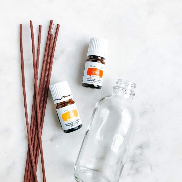 glass bottle laying next to brown reed diffusers and bottles of lemon and orange essential oils. Showing tools needed to make a reed diffuser